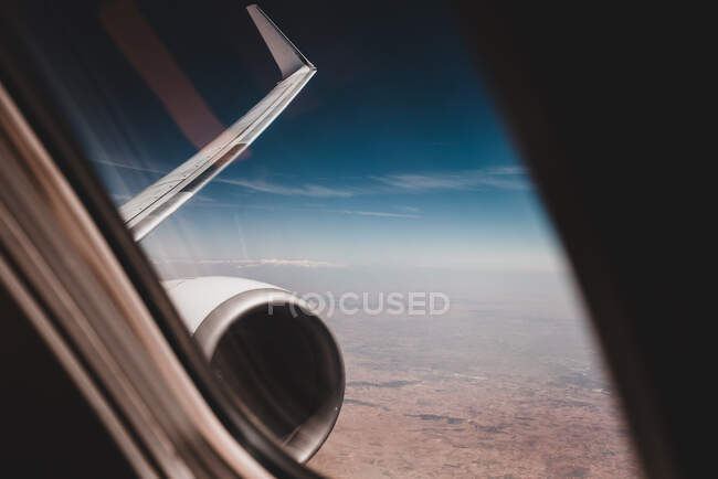 Blue sky and Earth through airplane window during flight — Stock Photo