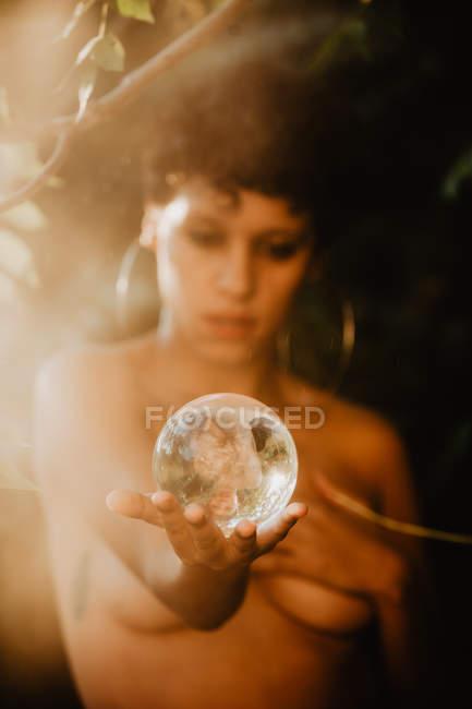 Молодая женщина топлес брюнетка охватывающих груди и проведение стеклянный прозрачный шар в зеленых лесах — стоковое фото