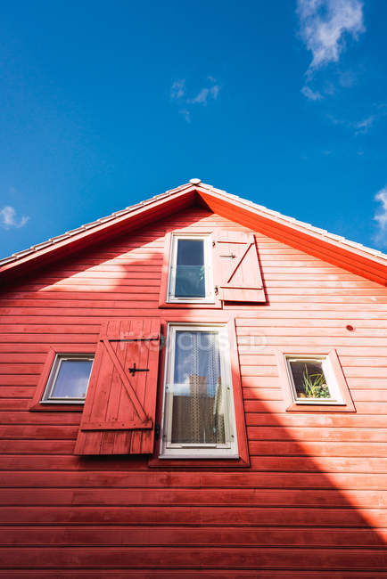 Windows with shutters on wooden red house on background of blue sky on sunny day — Stock Photo