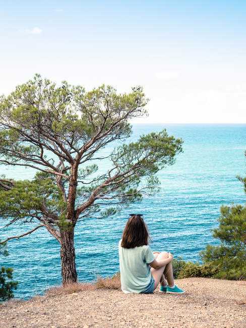 Woman sitting on cliff at blue seaside and looking at view — Stock Photo