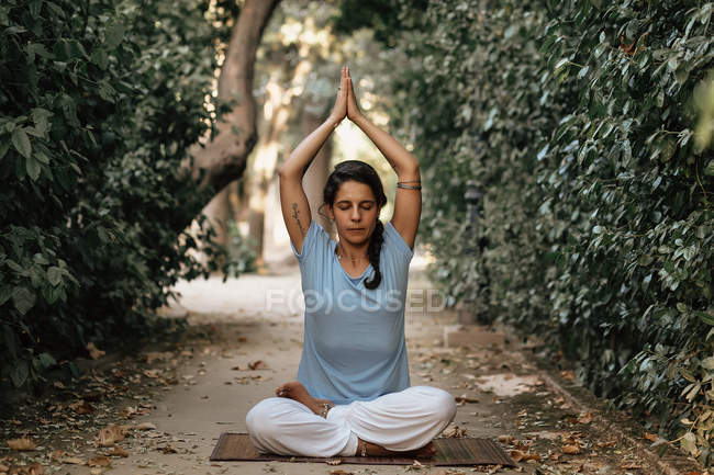 Tranquil woman doing yoga on path in autumn garden — Stock Photo