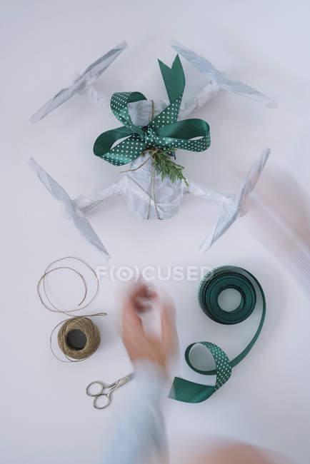 Masculinas mãos envolvendo o drone como presente de Natal com fita de abeto filial e verde sobre fundo branco — Fotografia de Stock