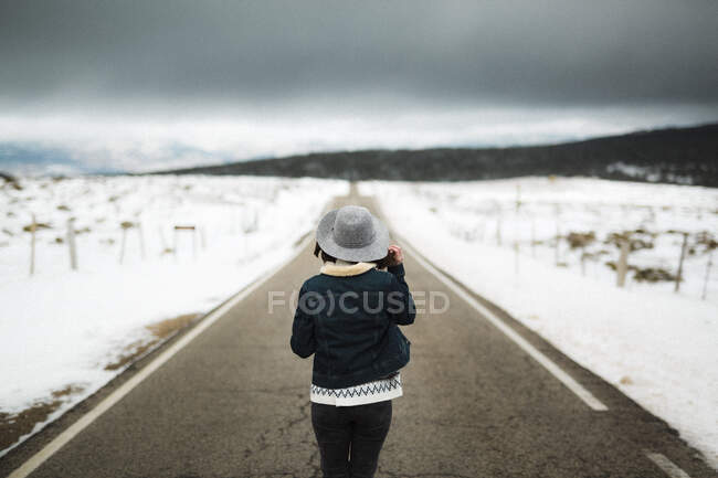 Back view of young person in stylish outfit walking in middle of asphalt road on cloudy winter day in beautiful countryside — Stock Photo