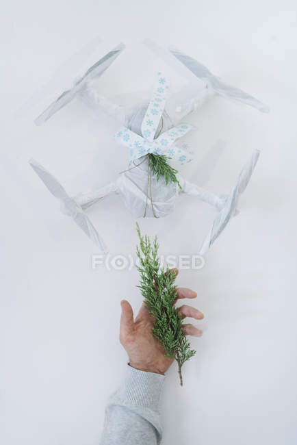 Male hand holding fir branch next to wrapped drone as Christmas gift on white background — Stock Photo