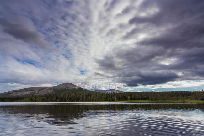 Landschaft von Bergen und grünen Wäldern in der Nähe von klaren plätschernden See vor dem Hintergrund des bewölkten Himmels — Stockfoto