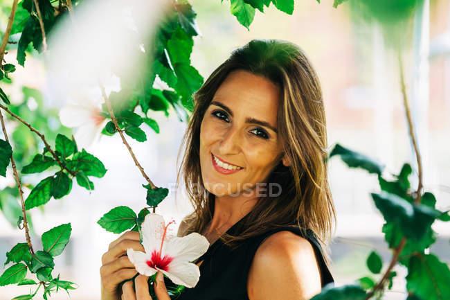 Porträt einer lächelnden stilvollen Frau, die unter einem Baum steht und Blumen im Park hält — Stockfoto