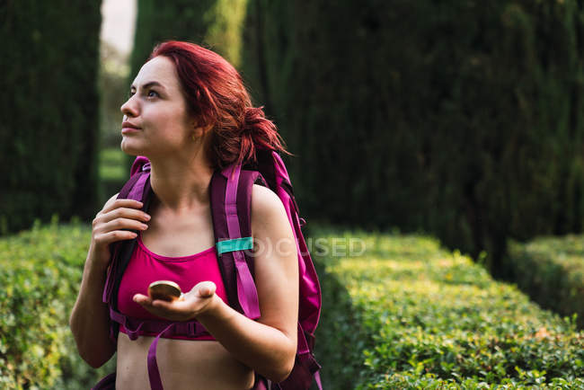 Woman with backpack and compass in hand walking in park — Stock Photo