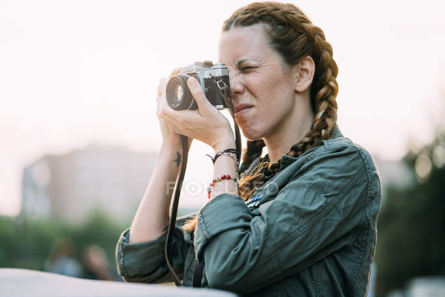 Pretty redhead girl with braids taking picture outdoors — Stock Photo