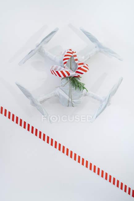 Drone embrulhado como presente de Natal com fita listrada de vermelha e branca em fundo branco — Fotografia de Stock