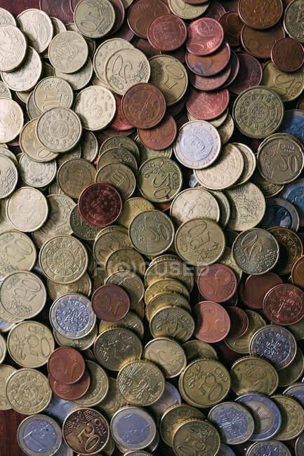 Из приведенного выше снимка коллекции различных монет, лежащих на столе — стоковое фото