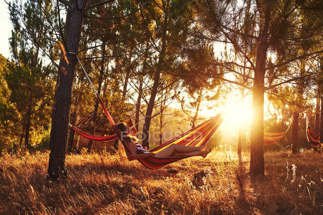 Femme couchée dans un hamac dans des bois ensoleillés — Photo de stock