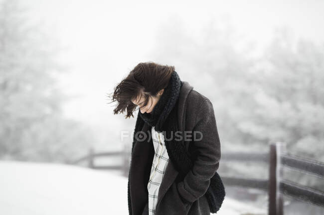 Side view of young female in warm clothes walking near fence on windy winter day in magnificent countryside — Stock Photo