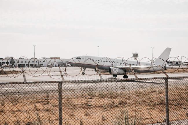 Aeroplano che sale dall'aeroporto racchiuso da filo di sicurezza, Mykonos — Foto stock