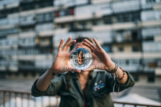 Woman holding crystal ball with reflection in city — Stock Photo