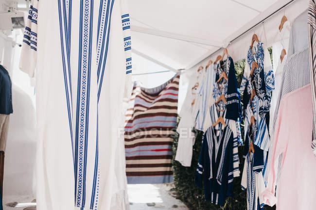 Diverse tuniche tradizionali su appendini di stoffa al mercato di strada, Mykonos, Grecia — Foto stock