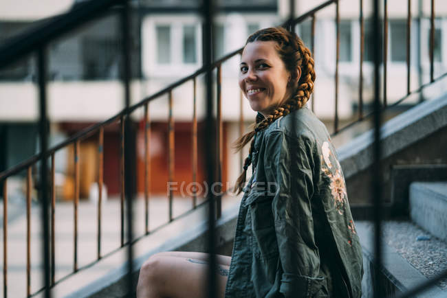 Smiling red-haired girl with braids sitting on staircase in city — Stock Photo
