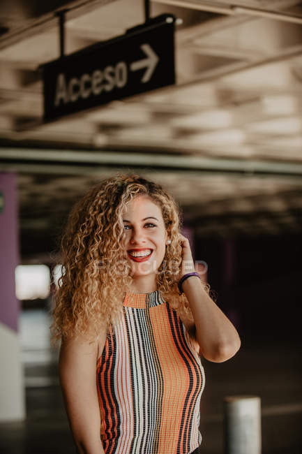 Portrait of smiling curly blond woman with bright lips in striped casual top — Stock Photo