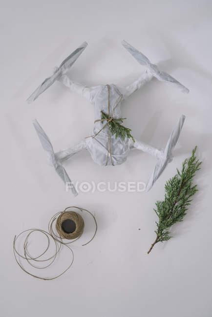 Drone embrulhado como presente de Natal com ramo de abeto e cordéis sobre fundo branco — Fotografia de Stock