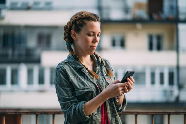 Chica pelirroja pensativa con trenzas que utilizan el teléfono móvil contra el edificio residencial - foto de stock