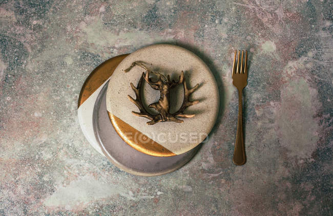 Christmas table set in white and gold colors decorated with figure of deer on concrete surface — стокове фото