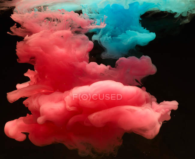 Pink and blue vivid smoke clouds on black background — Stock Photo