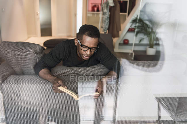 Focused African American man in glasses reading book while resting on sofa at home — Stock Photo