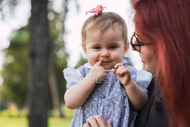 Mujer sosteniendo lindo bebé chica en parque - foto de stock