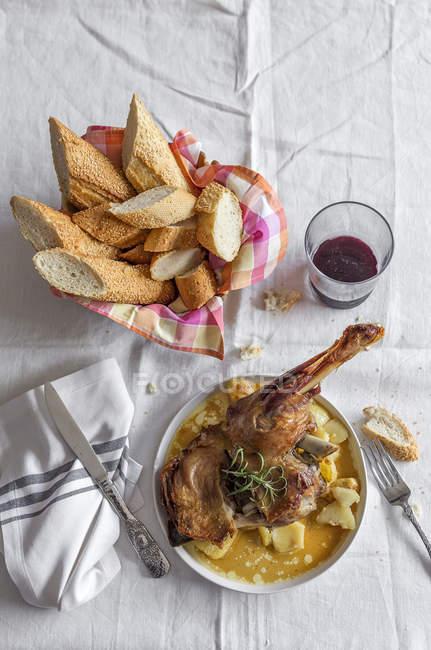 Cordeiro roasted com as batatas servidas na placa no tablecloth branco — Fotografia de Stock