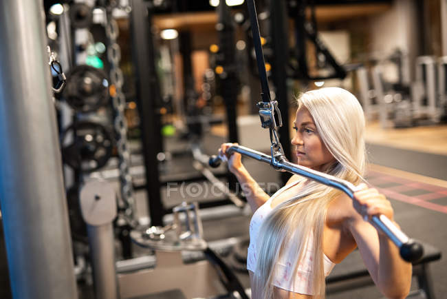 Fit blond woman doing exercise in gym — Stock Photo