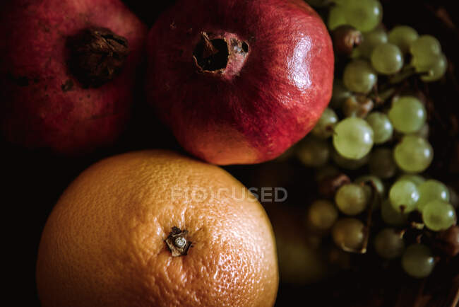 Composition of basket with oranges, grapes and pomegranates on table — Stock Photo