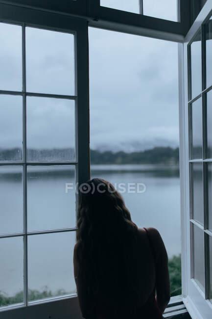 Mulher olhando através da janela do quarto — Fotografia de Stock