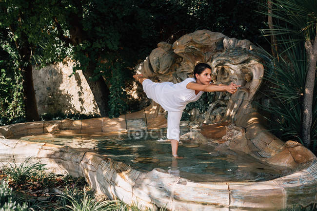 Woman standing in fountain water in Tree pose while doing yoga in park — Stock Photo