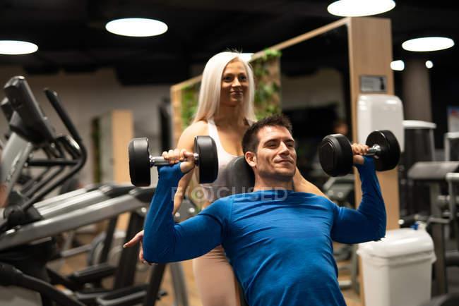 Женщина помогает мужчине делать упражнения с гантелями в спортзале — стоковое фото