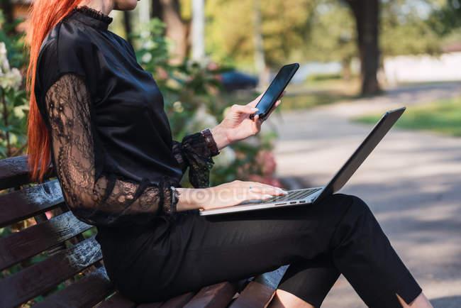 Mulher usando laptop e smartphone no banco no parque — Fotografia de Stock