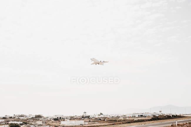 Знизу подання білий літак, що летить у хмарного неба над міста Міконос, Греція — стокове фото