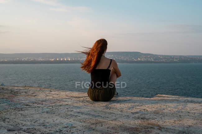 Задний вид юной леди, сидящей на бетонном берегу и любующейся прекрасным видом на спокойное море в ветреный день в Болгарии, на Балканах — стоковое фото