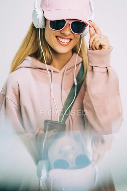 Elegante donna con cappuccio rosa e cappuccio ascoltare musica con le cuffie — Foto stock