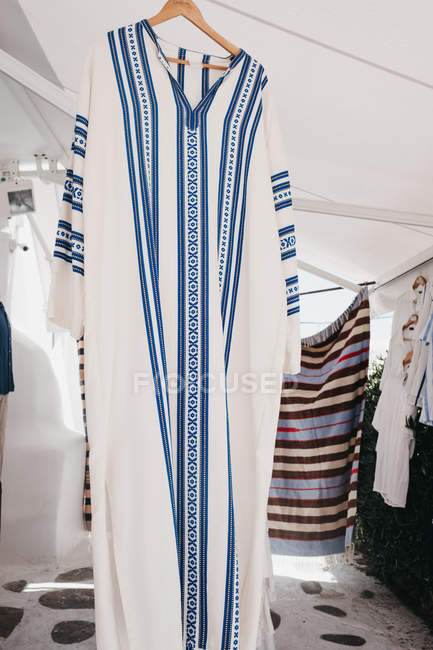 Different traditional tunics on cloth hangers at street market, Mykonos, Greece — Stock Photo