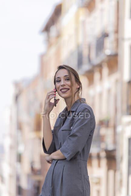 Femme gaie parlant sur smartphone dans la rue — Photo de stock