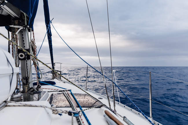 Detail of sailboat on high seas under cloudy sky — Stock Photo