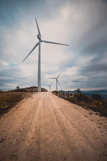 Rangée de moulins modernes debout sur le côté de la route de campagne étroite par temps nuageux — Photo de stock