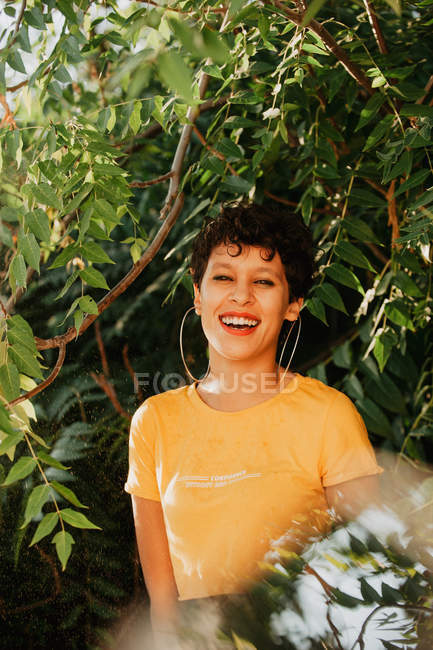 Portrait of smiling brunette with short hair standing in green vegetation with sunlight — Stock Photo