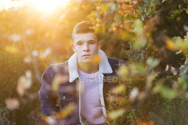 Retrato de adolescente en chaqueta de mezclilla de pie en arbustos soleados - foto de stock