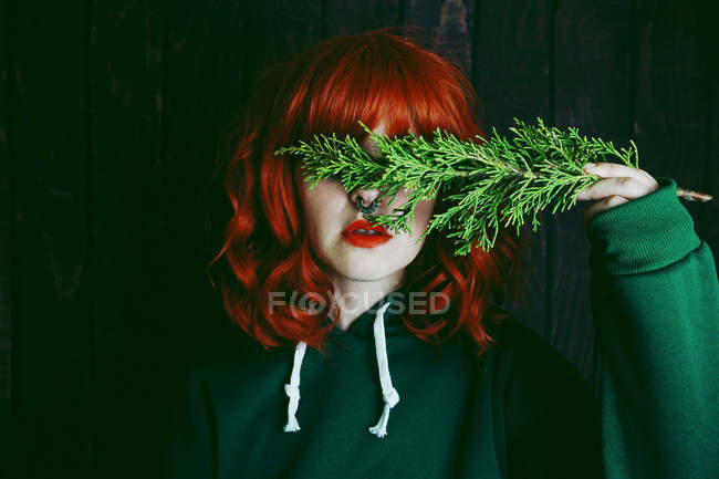 Young red haired woman covering eyes with green fir twig on black background — Stock Photo