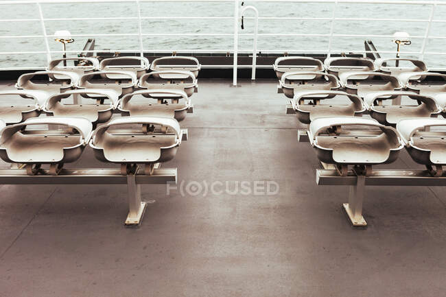Row of folded seats on empty deck of modern ship sailing in sea — Stock Photo