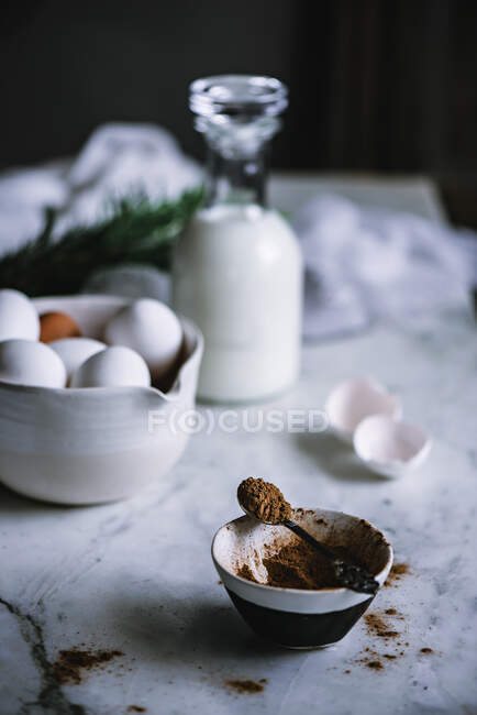 Чаша и ложка какао-порошка стоят на мраморном столе рядом с миской свежих яиц и бутылкой хорошего молочного продукта — стоковое фото
