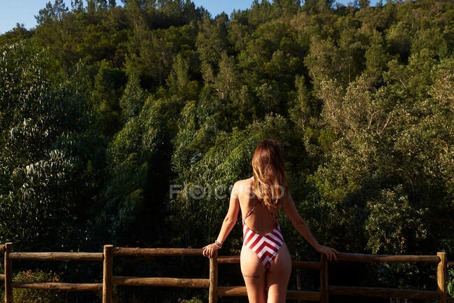 Unrecognizable woman with brown hair wearing red and whiter stripped swimwear standing on observation point and looking to thick green forest — Stock Photo