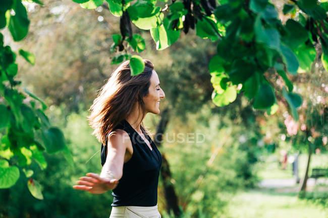Donna allegra in piedi sotto l'albero nel parco — Foto stock
