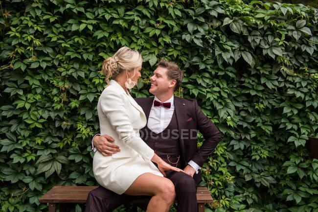 Зачаровані чоловік і жінка у модних весільних костюмах і дивляться один на одного проти зеленого живоплоту — стокове фото