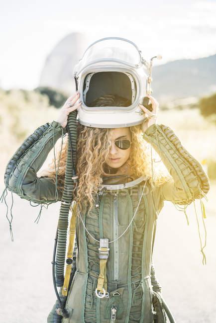 Confident woman in astronaut costume putting on helmet in sunlight — Stock Photo